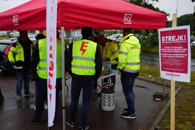 Strejkvakter i gula västar från Elektrikerna står under ett tält i regnet utanför Hometec Security Gbg i Göteborg