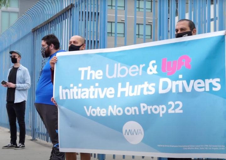 Fackliga gigarbetare protesterar med en stor blå banderoll mot gigföretagens lagförslag i Kalifornien. Banderollen uppmanar till att rösta nej till den kommande folkomröstningen.