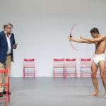 Två skådespelare i föreställningen Liv Strömquist tänker på sig själv. En ung man endast klädd i blöja siktar med leksakspilbåge mot en äldre man i Östermalmsmode.
