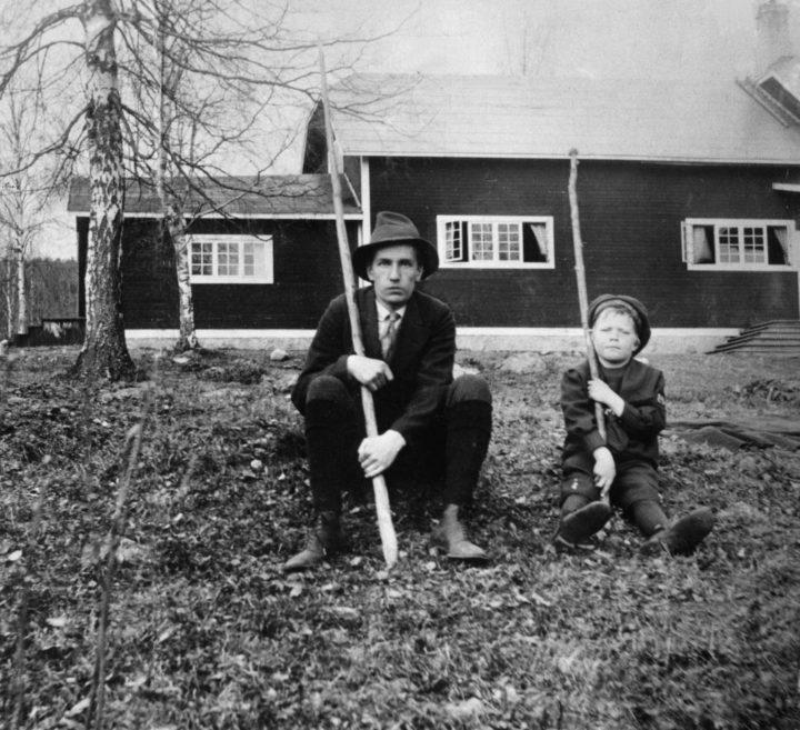 Svartvitt fotografi av Dan Andersson och en pojke som sitter på gräset utanför en Brunnsviks follhögskola.