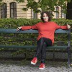 Mian Lodalen i röd tröja, svarta byxor och röda skor, sittandes på en grön bänk framför ett buskage, med benen i kors och armarna utsträckta längs ryggstödet.