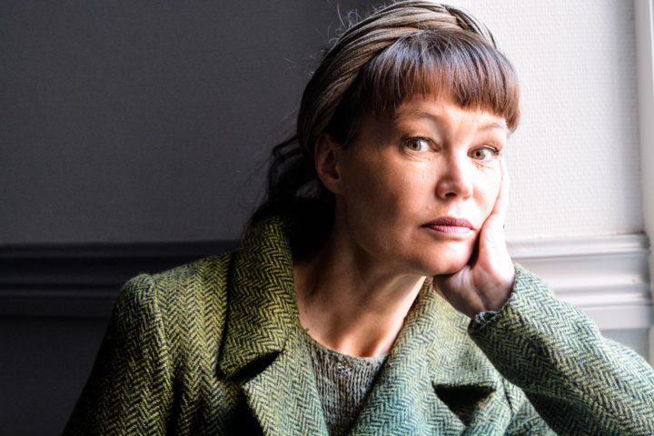 Nina Björk, med grön kavaj och hårband, lutar kinden mot sin hand och tittar in i kameran.