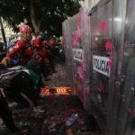 Rödklädda personer med hjälp står mellan demonstranter och poliser med plexiglassköldar som stänkts ned med rosa färg.