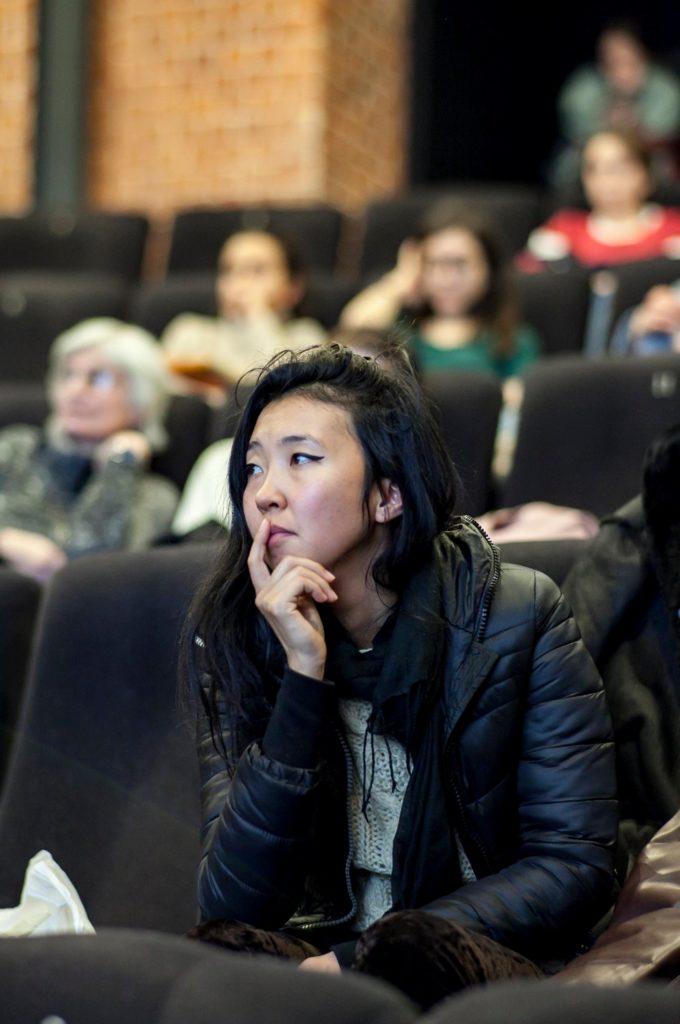 Den unga krigiziska statsvetaren Bermet Borubayeva i en föreläsningssal. Hon lutar hakan mot sin hand och ser ut att lyssna.