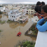 En familj tittar på förödelsen som orsakats av översvämningarna i Indien.