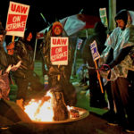 Strejkande bilfabriksarbetare värmer sig runt en brasa. Det är kväll eller natt och de håller skyltar med texten UAW on strike.