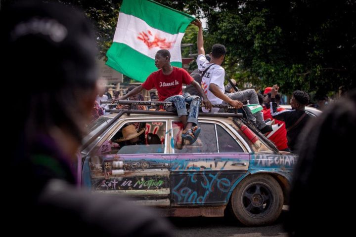 Två unga män sitter på ett biltak och håller i en grönvit flagga, Nigerias flagga. På gatan är fult av folk och bilen är nedklottrad med slagord.