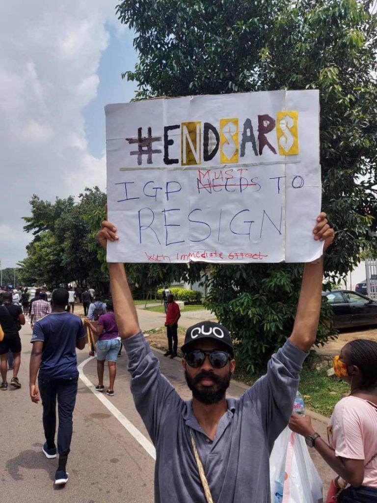 Theo Alonso håller upp en vit skylt med texten #EndSARS.