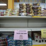 En butikshylla som gapar tom, skyltar med arabisk text uppmanar till boycott av franska varor.
