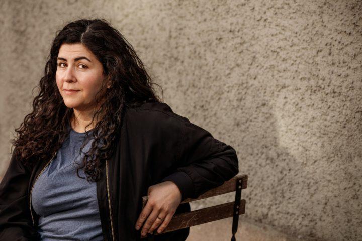 Farnaz Arbabi sittandes på en bänk med solbelyst ansikte.