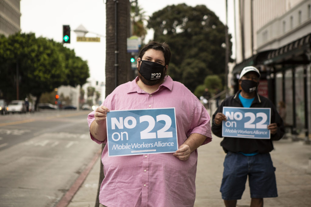 James West med munskydd med texten No on 22, håller en skylt där det står samma sak.