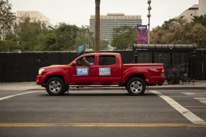 En röd pick-up-bil med texten No on 22 på dörren. Föraren håller en flagga där det står Unions for all.