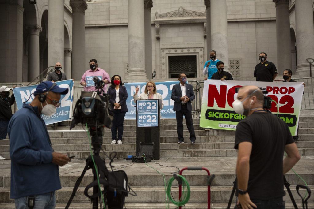 Senator Elena Maria Durazo lyfter fingret från talarstolen under demonstrationen mot proposition 22. Framför hennes står kameror.