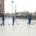 Städare i blåa skyddskläder svabbar golvet utanför en moské.