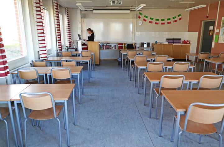 En lärare ensam framför en dator i ett klassrum där bänkarna står tomma.