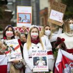 Kvinnor med vita kläder, håller rödvita flaggor, rosor och plakat där det bland annat står The future of Belarus is female.