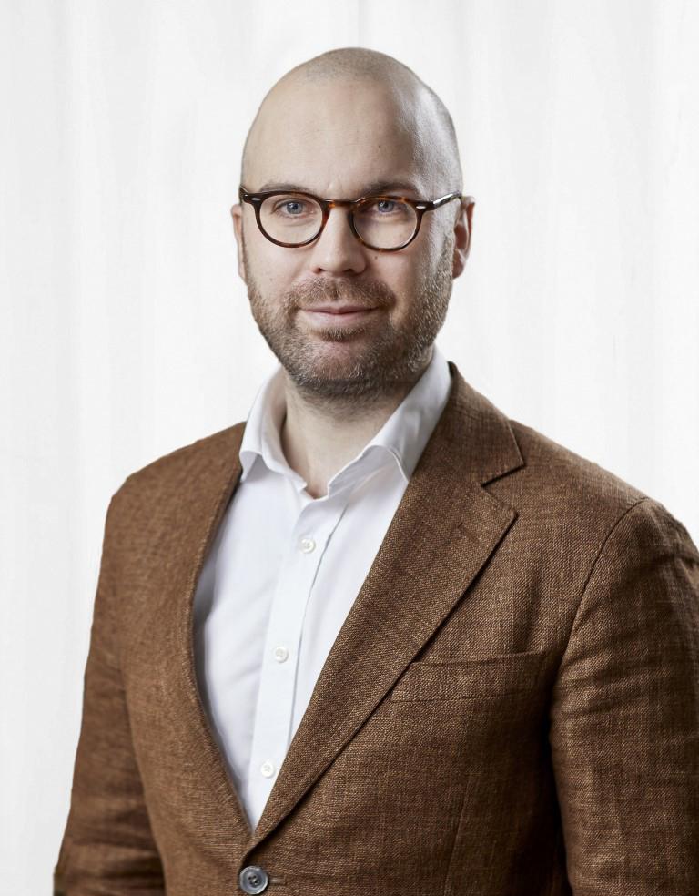 Porträttbild på Jonathan Öhman i brun kavaj och vit skjorta.