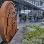 Entrén till Swedbanks huvudkontor i Sundbyberg. En skulptur av bankens logotyp, lite växtlighet och en glasfasad.