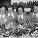 Tre kvinnor med mat och frukt framrör sig på en historisk bild.