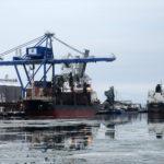 Oxelösunds hamn i januariväder. Bilden visar en blå kran och tre skepp vid kaj