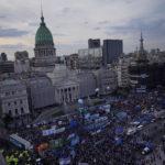 Flygfoto över torget framför den argentinska kongressen. Torget är fyllt av demonstranter med skyltar och ballonger.