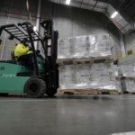En lagerarbetaren i gul jacka kör en gaffeltruck lastad med två fulla pallar med vaccin.
