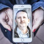Två händer håller fram en mobiltelefon som visar ett porträtt av Ahmadreza Djalali.