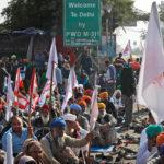 """Indiska bönder sitter på marken framför en skylt med texten """"Välkommen till Delhi"""""""