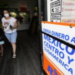 En kvinna och ett barn, båda med munskydd, lämnar en butik. På en skylt står det på spanska att man här kan skicka pengar till Central- och Sydamerika.