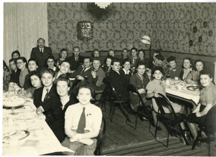 Svartvitt fotografi där en mängd människor sitter samlade kring två bord och tittar in i kameran.