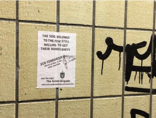 Affisch från The Green brigade uppsatt på en gul kakelvägg. Affischen promotar ekoterrorism.