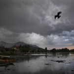 Mulen himmel speglas i en sjö. En örn syns på himmelen.