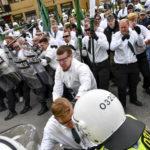Nazistiska organisationen Nordiska motståndsrörelsen (NMR) demonstration i Kungälv på första maj 2019. De är klädda i vita skjortor och gröna slipsar och har gröna flaggor och plexiglas-sköldar.