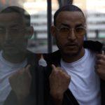 Ali, 31 år, står vid en glasruta där han reflekteras.