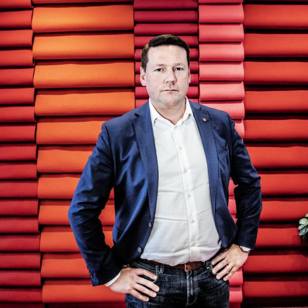 Tobias Baudin med händerna i sidorna framför en röd vägg.