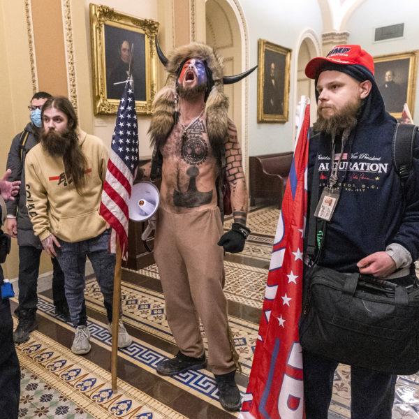Fyra Trumpsupportrar utanför senatskammaren, inne i Kapitoleum. En av dem har buffelhorn på huvudet, päls över axlarna och många tatueringar.