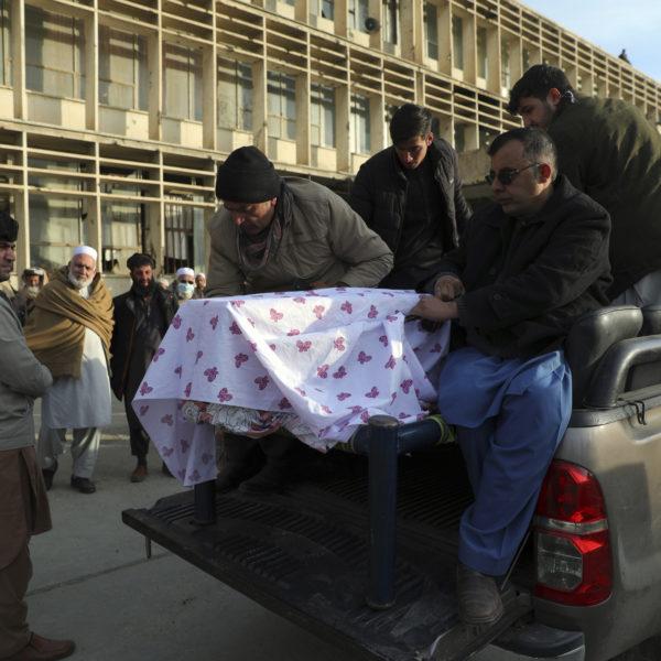 Fyra män lyfter av en kista täckt av ett vitt tyg, från flaket av en bil.