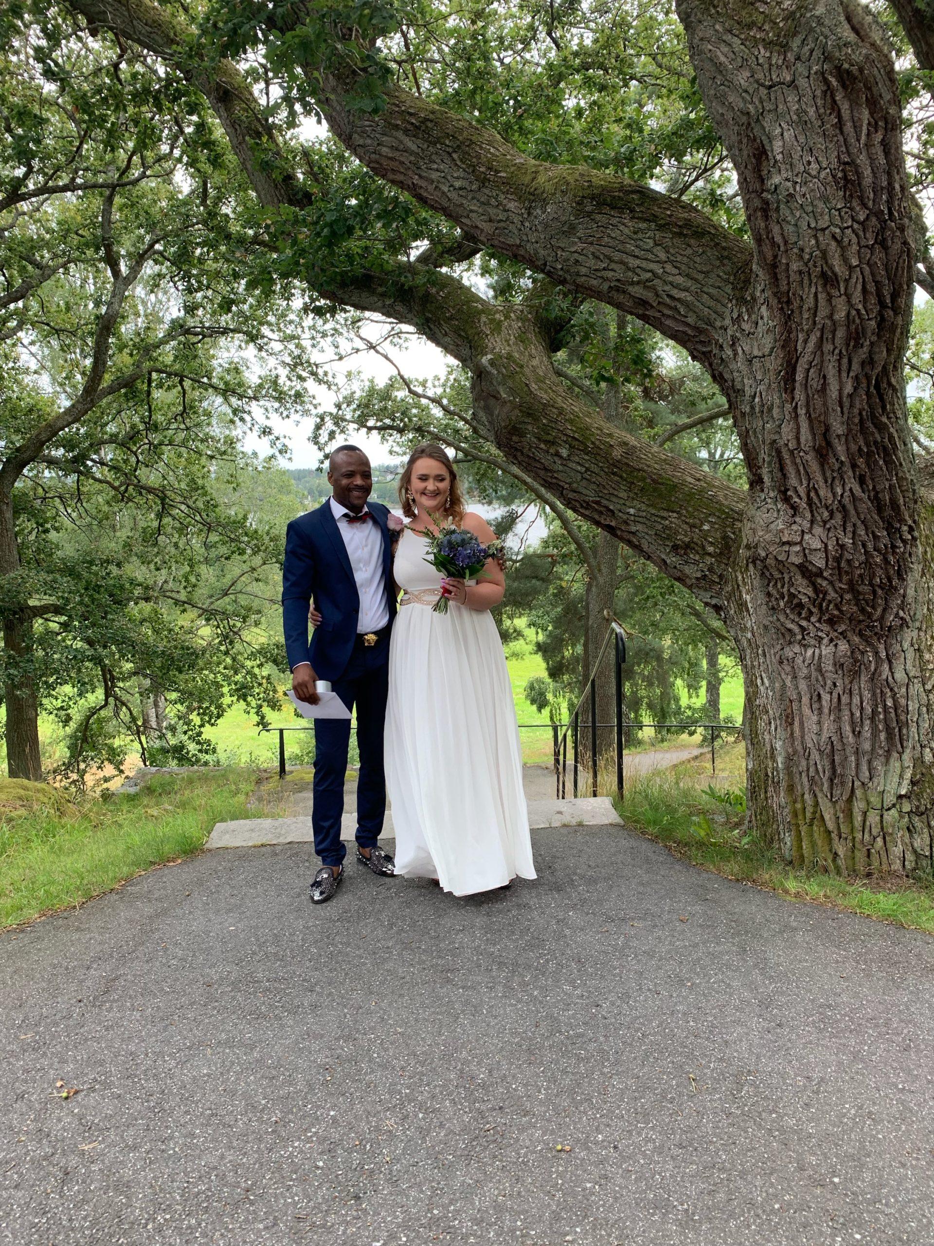 David och Johanna klädda för bröllop bredvid ett stort grönskande träd.