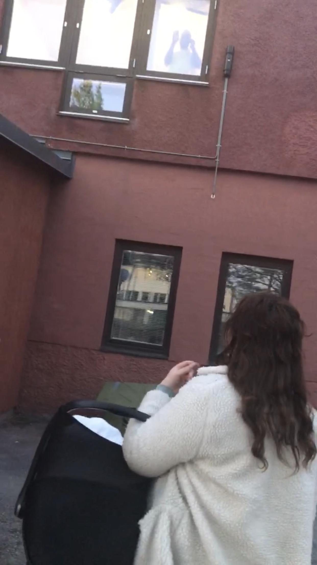 Johanna står med en bilbarnstol på armen och tittar upp mot ett fönster på andra våningen, där David tittar ut.