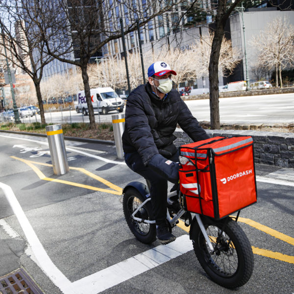 Cykelbud med en röd matförvaringslåda på styret, keps och munskydd, cyklar på en gata.