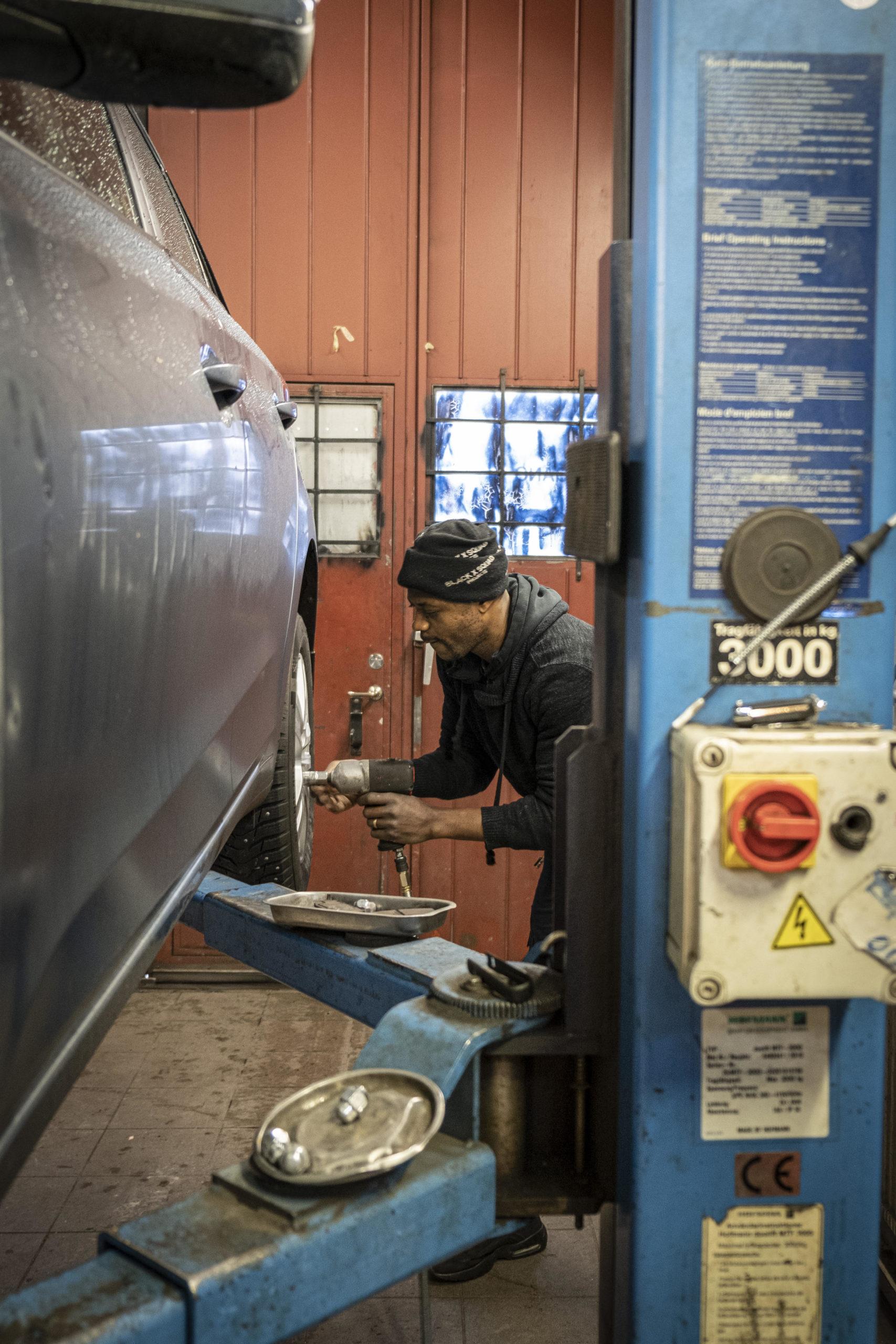 David skruvar fast däcken på en bil som hänger upphissad. Verkstadsmiljö.