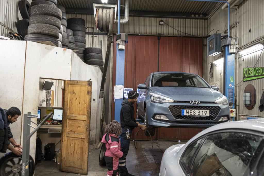 David fäster ett hjul på en upphissad bil i verkstaden. Hans äldsta dotter tittar på i rosa overall. En kollega rullar in ytterligare ett hjul.