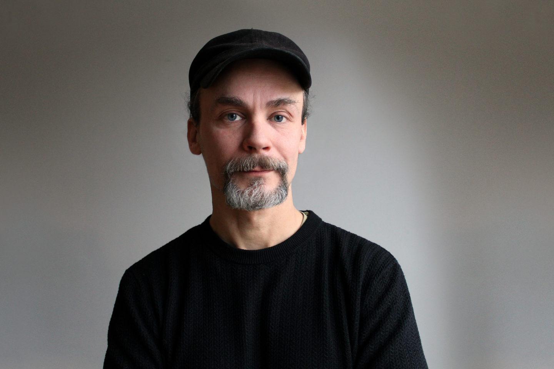 Emil Boss i svart tröja och keps mot ljusgrå bakgrund