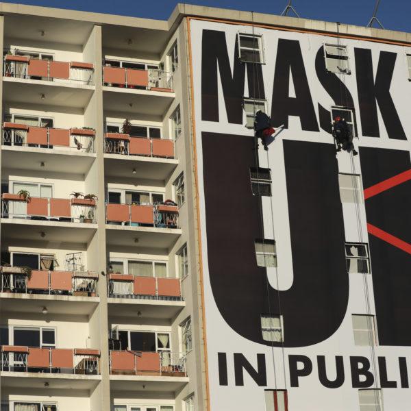 En reklamtavla som täcker en husfasad. Texten lyder Mask up in public.