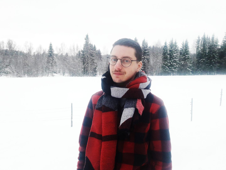 Nino Mick fotograferad i ett snöigt landskap med en stor halsduk runt halsen.