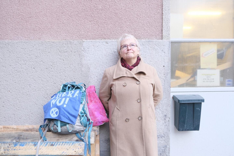 """Anna Termine lutar sig mot en vägg. Bredvid sig har hon sin väska, som det står """"Agera nu!"""" på."""