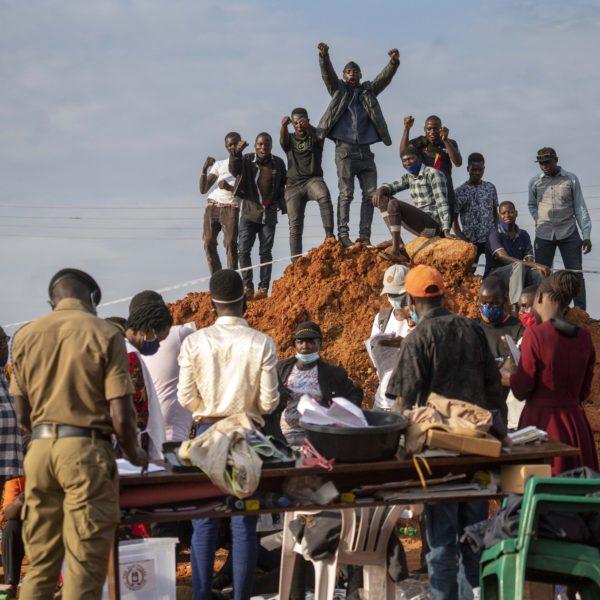 Supportrar till oppositionskandidaten Bobi Wine sträcker upp armarna i luften.
