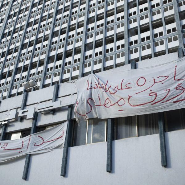 En husfasad i Tunis med två vita banderoller med röd arabisk text.
