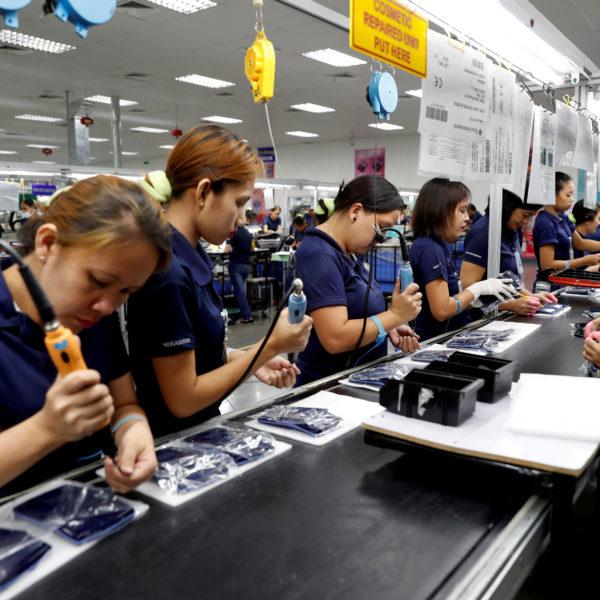 Kvinnor i blåa kläder arbetar med elektroniktillverkning.