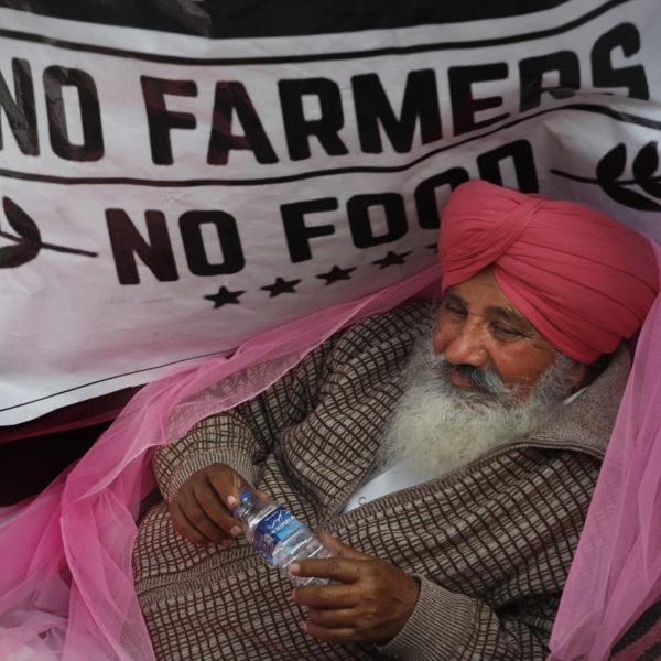 En bonde med en hallonröd turban och en rosa sjal över axlarna lutar sig framför en banderoll med texten No farmers no food.